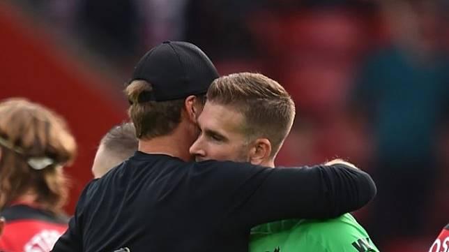 Kiper Liverpool, Adrian San Miguel berpelukan dengan Jurgen Klopp setelah laga antara Southampton vs Liverpool di Stadion St Mary's, Sabtu (17/8.2019). (GLYN KIRK / AFP)