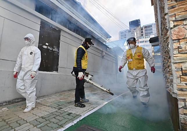 A South Korean health worker sprays disinfectant as part of preventive measures against the spread of the COVID-19 coronavirus, at a residential area near the Daegu branch of the Shincheonji Church of Jesus in Daegu on February 27, 2020. - South Korea now has 1,766 cases, the highest number in the world outside China, where the disease first emerged in December and has since spread to dozens of countries.