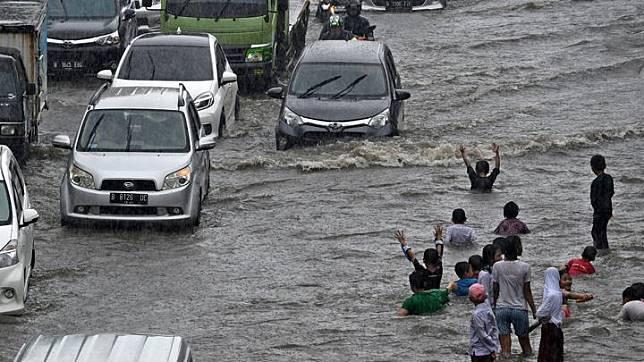 Sejumlah pengendara kendaraan bermotor melintasi Jalan Gunung Sahari yang mengalami banjir di Pademangan, Jakarta, Jumat 24 Januari 2020. Hujan yang mengguyur sejak Jumat pagi hingga siang hari tersebut memicu banjir setinggi 30-50 centimeter di jalan raya itu sehingga menyebabkan lalu lintas kendaraan bermotor dan roda perekonomian warga setempat tersendat.  ANTARA FOTO/Aditya Pradana Putra