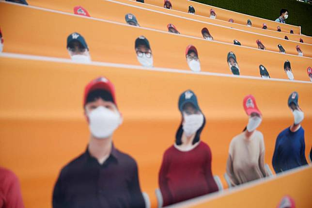 Baseball - KBO Regular season - SK Wyverns v Hanwha Eagles - Munhak Baseball Stadium, Incheon, South Korea - May 5, 2020   A man wearing a face mask is seen behind the dummies replacing the audience before the match, despite most sports being cancelled around the world the local league starts behind closed doors due to the spread of the coronavirus disease (COVID-19)