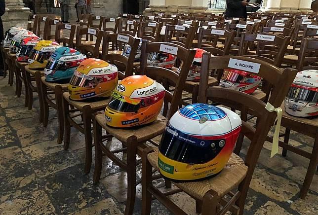 Helm pembalap berjejer di atas kursi di dalam katedral saat upacara pemakaman pembalap F2 Anthoine Hubert