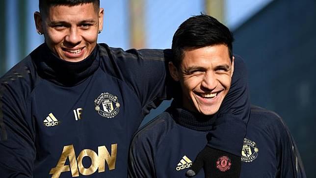 Pemain Manchester United, Marcos Rojo dan Alexis Sanchez, tersenyum saat latihan jelang laga 16 besar Liga Champions. (AFP/Franck Fife)