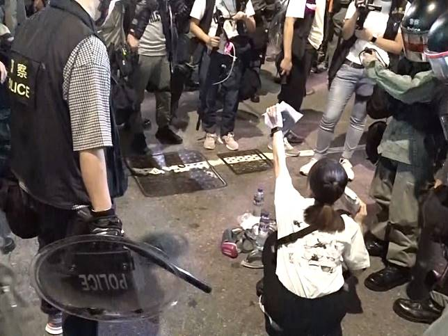 有女子被警方要求即場搜查隨身物品。(鄭鈞祺攝)