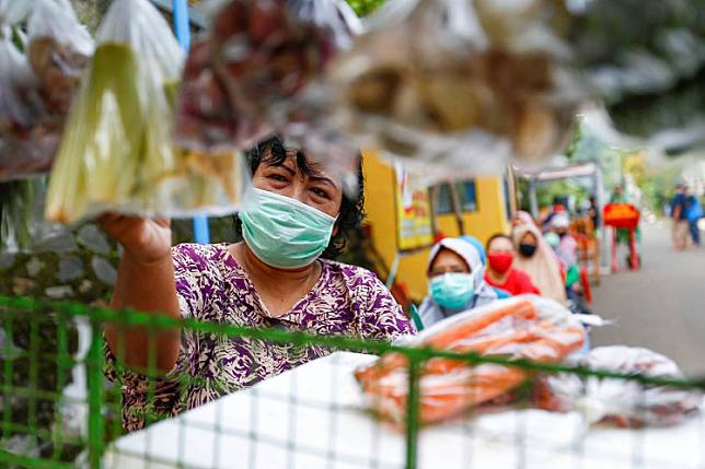 People practice physical distancing while buying vegetables amid the COVID-19 outbreak in Depok, West Java, on April 28.