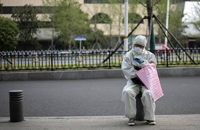 A woman wearing a protective suit uses her mobile phone on a street in Wuhan, in China's central Hubei province on April 3, 2020.