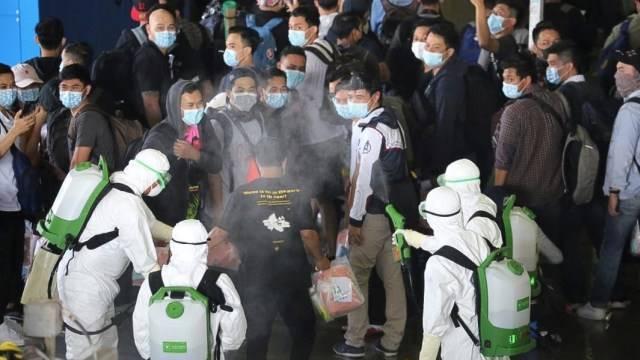 Petugas menyemprotkan cairan desinfektan kepada WNI kru kapal World Dream saat menaiki KRI dr Soeharso yang difasilitasi TNI AL, di Selat Durian Kepulauan Riau. Foto: ANTARA FOTO/Dispenal
