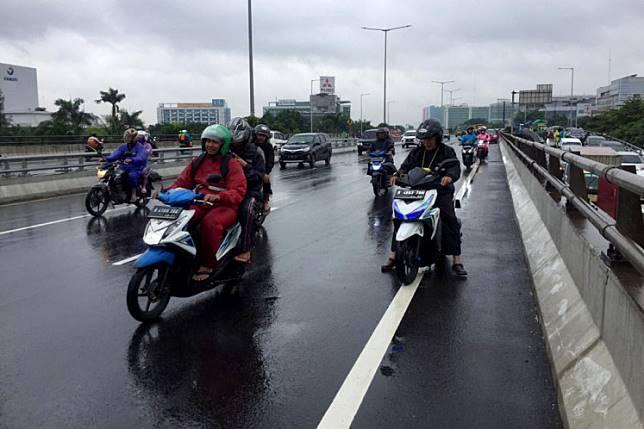 Motorists use the Cempaka Putih overpass to avoid floods on Tuesday.