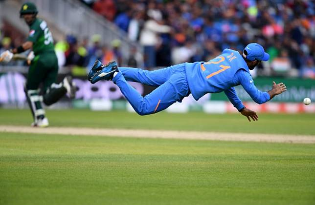 India's Dinesh Karthik dives as he throws the ball in a run out attempt during the 2019 Cricket World Cup group stage match between India and Pakistan at Old Trafford in Manchester, northwest England, on June 16, 2019.