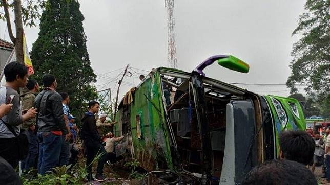 Bystanders look at a wrecked tour bus in Cisaat village, Ciater district, Subang, West Java. The bus  overturned while it was navigating the slope in the area, killing eight on board.