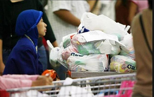A customer of a supermarket pushes a trolley full of goods in plastic bags.