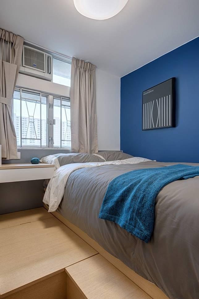 主人房彩藍色的特色牆貫徹全屋主題色調,配合灰色床頭背板,感覺悠然閒適;加建木地台,為室內增添大量儲物空間。 (受訪者提供)