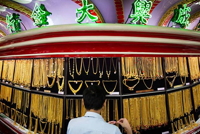 A shop assistant organises a display of gold jewelry at the
