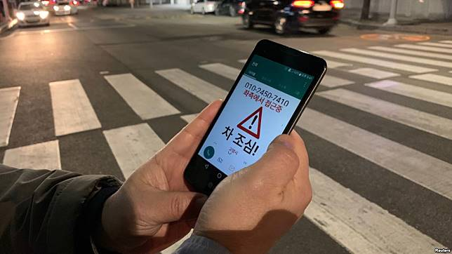 A researcher demonstrates an application that gives an alert to a user distracted by using smart phone while crossing a zebra crossing, in Ilsan, South Korea, March 12, 2019.