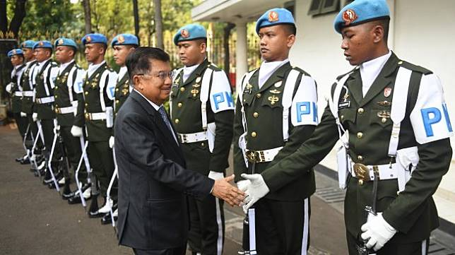 Wakil Presiden Jusuf Kalla berjabat tangan dengan anggota Pengawal Istana dari satuan Yonwalprotneg Paspampres sebelum meninggalkan Istana Wakil Presiden pada hari terakhirnya bertugas di Jakarta, Sabtu (19/10). [ANTARA FOTO/Akbar Nugroho Gumay]