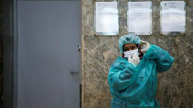 A journalist wears a protective suit during a media visit to Indonesian Health Ministry's Laboratorium for Research on Infectious-Diseases, following the outbreak of the new coronavirus in China, in Jakarta, Indonesia, February 11, 2020. Dozens of cases have been recorded in other regional countries including Singapore, Malaysia, Thailand, Vietnam and the Philippines, where one person has died, raising suspicions on social media in particular over a potential lack of vigilance in Indonesia. REUTERS/Willy Kurniawan