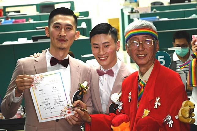 Taiwan's gay activist Chi Chia-Wei (R) signs a wedding certificate for gay couple Shane Lin and Marc Yuan (L) after registering at the Household Registration Office in Shinyi District in Taipei on May 24, 2019.