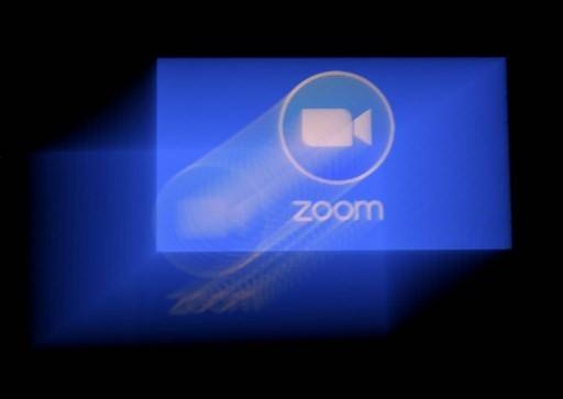 In this file photo illustration taken on March 29, 2020,  Zoom app logo is displayed on a smartphone, in Arlington, Virginia.  Zoom, which has seen its popularity skyrocket in the coronavirus pandemic, is in hot water after users complained to the FBI of being startled by porn during meetings