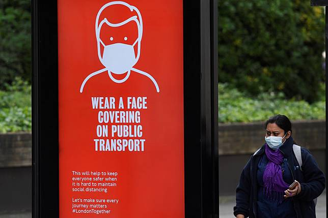 A woman wearing a protective face mask is seen at a bus stop with a public health campaign advertisement asking for passengers to wear masks on public transport, following the outbreak of the COVID-19, London, Britain, May 17, 2020 .The number of suspected and confirmed deaths from coronavirus in Britain has risen to 48,000, official data showed Tuesday.
