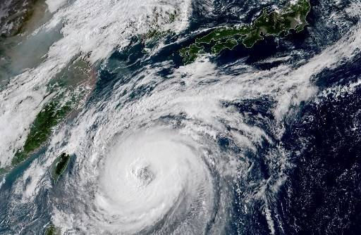 This NOAA/RAMMB satellite image taken at 23:30 UTC on September 27, 2018, shows Typhoon Trami off the Japanese south coast in the Philippine Sea.  A large, very strong typhoon churned towards Japan Friday, with the weather agency warning the storm would rip through the nation over the weekend, bringing violent winds and torrential rain. Typhoon Trami, packing gusts of a maximum 162 kilometers per hour near its centre, was in the Pacific spiralling slowly towards Japan's southern islands.
