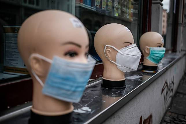Various protective face masks, worn by many people during the new coronavirus COVID-19 pandemic, are on display for sale outside a shop in Berlin's Kreuzberg district on April 2, 2020.