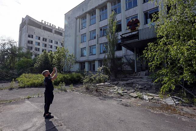 A visitor takes photos of a building in the abandoned city of Pripyat, near the Chernobyl nuclear power plant, Ukraine June 2, 2019.