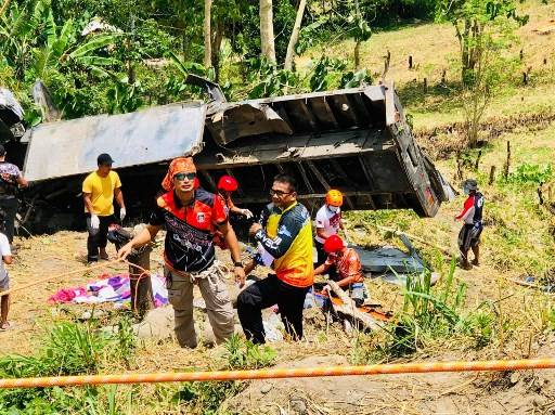 In this photo taken by Michael Acas and downloaded from the facebook account of Rolly Aquino shows rescue workers standing next to a flatbed truck after it fell into a ravine in T'Boli town, South Cotabato province,in southern island of Mindanao on September 17, 2019. Fifteen people, including children, were killed on September 17 in the southern Philippines when a flatbed truck they were riding in plummeted into a ravine, police said.
