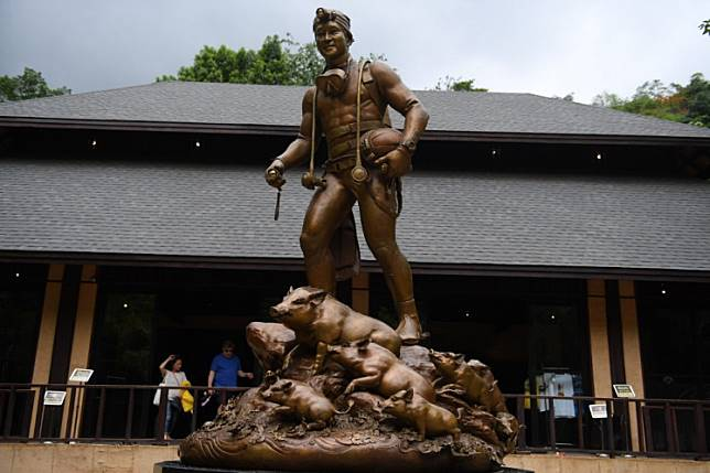 """a statue of Saman Gunan, the Thai navy diver who died during the rescue effort of the """"Wild Boars"""" football team and their coach, at the Tham Luang cave visitor centre in the Mae Sai district of Chiang Rai province. Tourists snap selfies by a bronze statue of the diver who died trying to save the 'Wild Boar' footballers from a flooded cave, while momentos from their rescue fly off the shelves -- scooped up by the 1.3 million people who have descended on a once serene mountainside in northern Thailand."""