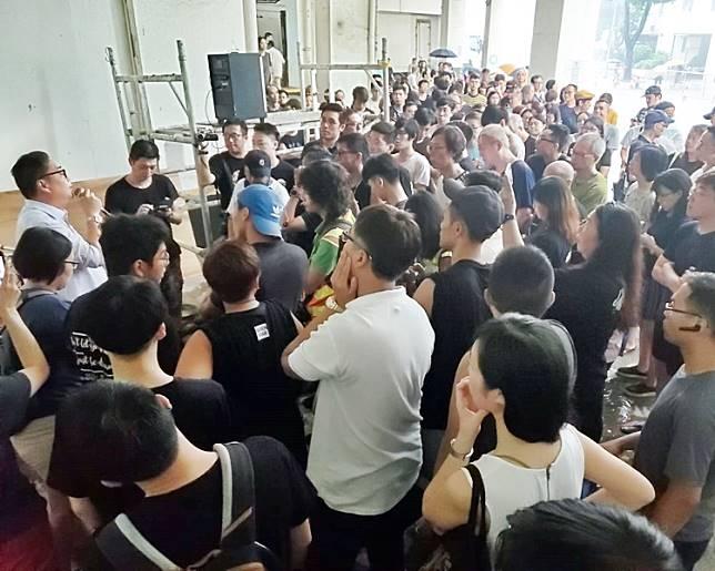 蘇冠成(左,淺色上衣)在場向居民解釋。