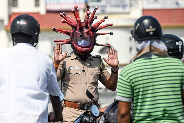 Police inspector Rajesh Babu in Chennai, India, wears a coronavirus-themed helmet as he speaks to motorists at a checkpoint during a government-imposed nationwide lockdown as a preventive measure against the coronavirus pandemic on March 28. A similar method is used by traffic police in Mojokerto, East Java.