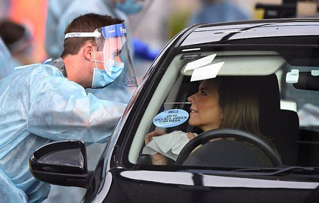 A member of the Australian Defence Force takes a swab sample at a drive-through COVID-19 coronavirus testing station in the Melbourne suburb of Fawkner on July 2, 2020. - Around 300,000 people in Melbourne have to return to lockdown under the threat of fines and arrest as Australia's second biggest city attempts to control a spike in virus cases. Health workers went door-to-door in the 36 Melbourne neighbourhoods targeted for lockdown, urging residents to be tested for the coronavirus.