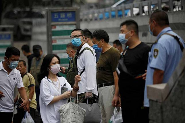 People wearing face masks wait at a bus stop during morning rush hour, following the outbreak of the coronavirus disease (COVID-19), in Beijing, China July 13.