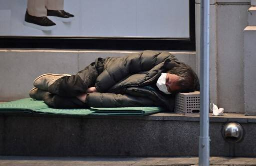 A homeless man wearing a face mask sleeps on the sidewalk at Dongseongro shopping district in the southeastern city of Daegu on Feb. 24.The number of coronavirus cases in South Korea rose to 893 on Tuesday, as health authorities said they plan to test potentially more than 200,000 members of a church at the epicenter of the outbreak.