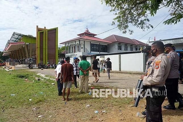 Petugas kepolisian berjaga saat membubarkan kerumunan warga yang menyaksikan pertandingan sepak bola di Lapangan Hoki Sorong, Papua Barat, Jumat (7/5/2021). Kepolisian Sorong Kota membubarkan kerumunan massa tersebut yang mengabaikan protokol kesehatan di masa pandemi COVID-19.