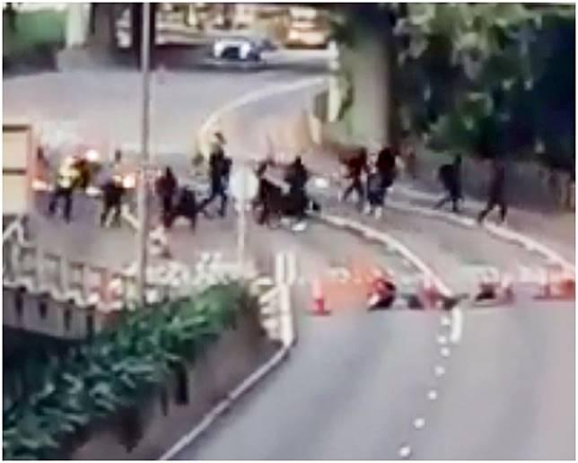 黑衣人以汽油彈在馬路上伏擊兩名交通警員。網圖