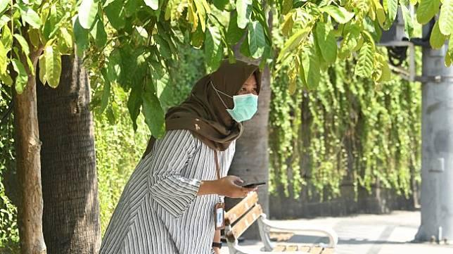 Warga berteduh di bawah pohon saat akan melakukan aktivitas di kawasan Bundaran Hotel Indonesia, Jakarta, Selasa (22/10). [ANTARA FOTO/Muhammad Adimaja]
