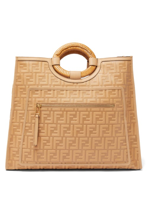 Fendi - Fendi's beige leather Runaway tote bag is embossed with the iconic FF logo, first conceived by Karl Lagerfeld in 1965. Crafted in Italy, it features elliptical basket-weave top handles and a zipped front pocket, then opens to reveal butter-soft suede lining. Offset the muted hue by styling it with a blue tailored ensemble.