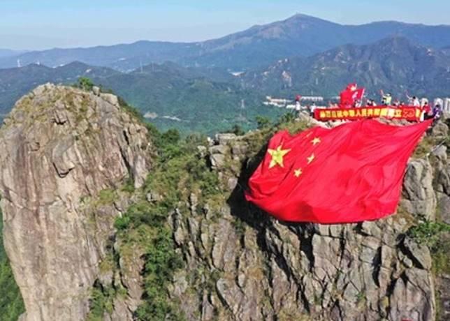 有民眾將大型五星旗掛在獅子山山頂。(互聯網)