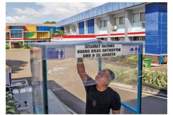 Petugas keamanan memeriksa bilik disinfeksi di pintu masuk SMKN 26 Rawamangun, Jakarta Timur, kemarin.