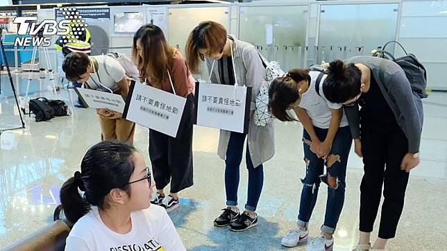 空服員身上披掛「請不要責怪地勤」的標語,在長榮櫃檯前鞠躬致歉,地勤僅點頭示意 圖/TVBS