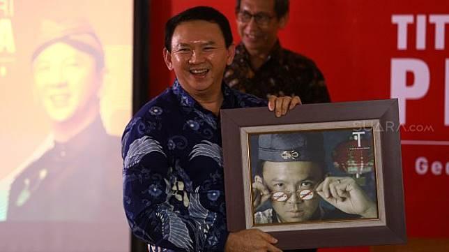 Basuki Tjahaja Purnama menerima cenderamata saat peluncuran buku 'Panggil Saya BTP: Perjalanan Psikologi Ahok Selama di Mako Brimob' di Gedung Tempo, Palmerah, Jakarta, Senin (17/2). [Suara.com/Angga Budhiyanto]