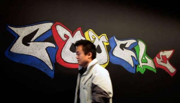 Seorang pria melewati logo Google yang digambar menggunakan kapur tulis di Google campus dekat Pantai Venice, Los Angeles, California. Di tempat ini, sekitar 500 orang pekerja mendesain iklan video untuk situs YouTube, beberapa bagian jejaring sosial Google+ dan alat penjelajah Chrome. REUTERS/Lucy Nicholson