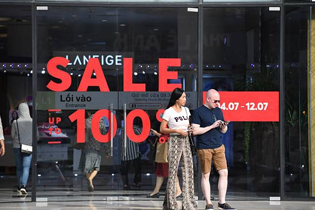 People wait for a taxi outside a shopping mall holding sale promotions in Hanoi on July 6, 2020.