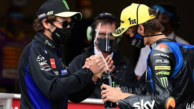 Luca Marini (kanan) mendapat sambutan dari sang kakak, Valentino Rossi ketika finis tiga besar pada salah satu balapan Moto2 2020. (LLUIS GENE / AFP)