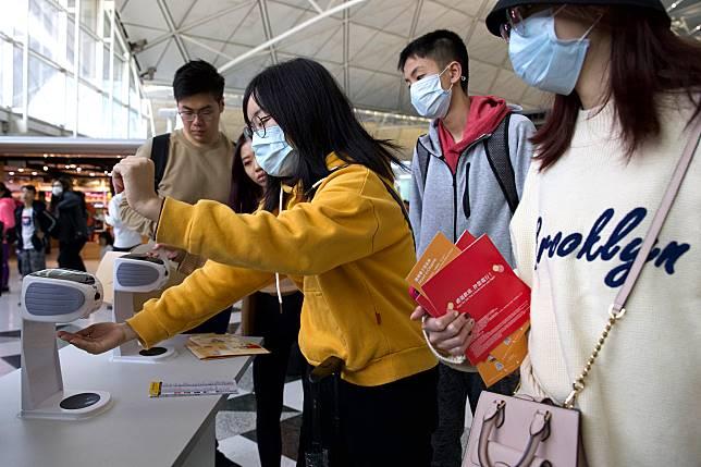 ▲俗稱武漢肺炎的「 2019 新型冠狀病毒」疫情擴散中,亞洲多國已出現疑例或確診。圖為近期香港機場旅客使用口罩與消毒設備。(圖/美聯社/達志影像)