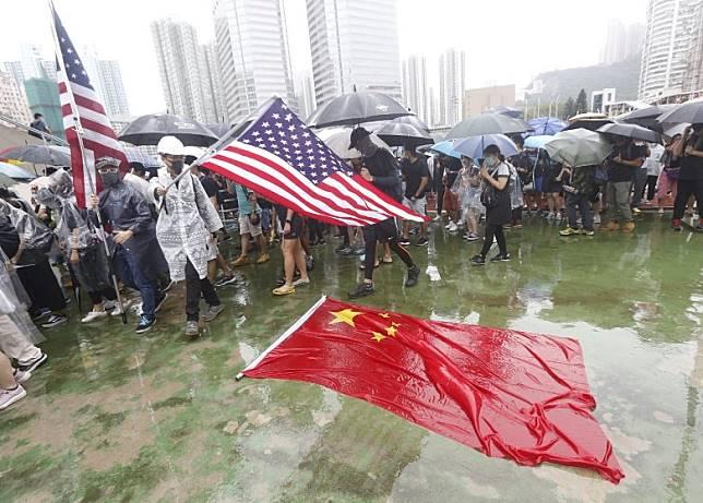 有示威者揮動美國國旗。(何天成攝)