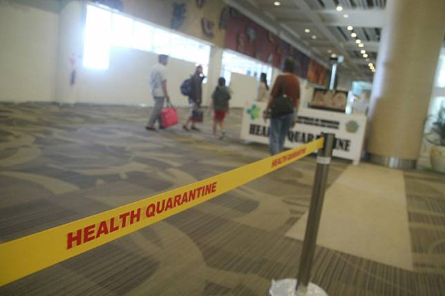 A number of passengers at Ngurah Rai International Airport walk past the thermal scanner from the Port Health Office (KKP) on Jan. 22.