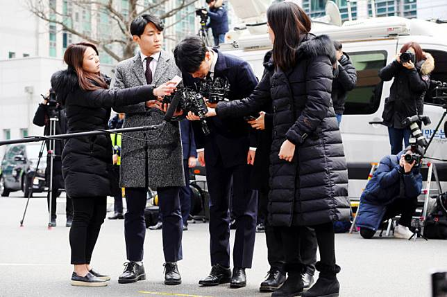 Shamed: Seungri (center), a member of the K-pop boy group BIGBANG, bows as he arrives for questioning over criminal allegations at the Seoul Metropolitan Police Agency in Seoul on March 14. Seungri on March 11 announced his retirement from show business amid mounting criminal investigations including his alleged involvement in a sex-for-investments scandal.