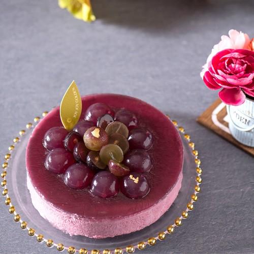 來自大村巨峰葡萄的春暖氣息~被譽為「葡萄之王」的巨峰葡萄色澤黝黑迷人,果汁濃厚甜美。「巨峰‧王漾」嚴選葡萄汁製成果凍,如紫紅晚霞泛著點點繁星。內層幼滑的綜合莓果慕絲配以濃厚朱古力蛋糕,口感細膩。底層夾