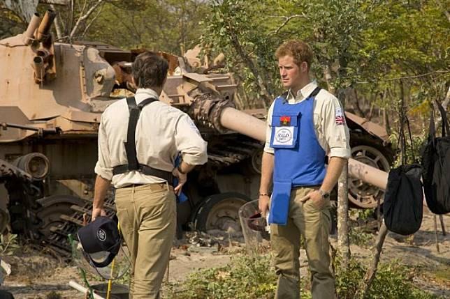 Britain's Prince Harry (R) and HALO Director Guy Willougby stand next to a South African Olifant tank destroyed in the battle for Cuito Cuanavale in 1988, in Angola, in this undated handout photograph released in London August 18, 2013.