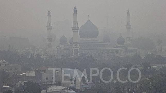 Salah satu rumah ibadah di Kota Pekanbaru dengan latar belakang kabut asap yang berasal dari kebakaran hutan dan lahan di Pekanbaru, Riau, Rabu, 18 September 2019.  Lahan gambut di Rimbo Panjang kembali terbakar besar karena cuaca panas dan tiupan angin. TEMPO/Hilman Fathurrahman W